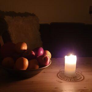 levende lys og frugtskål på bord i mørket